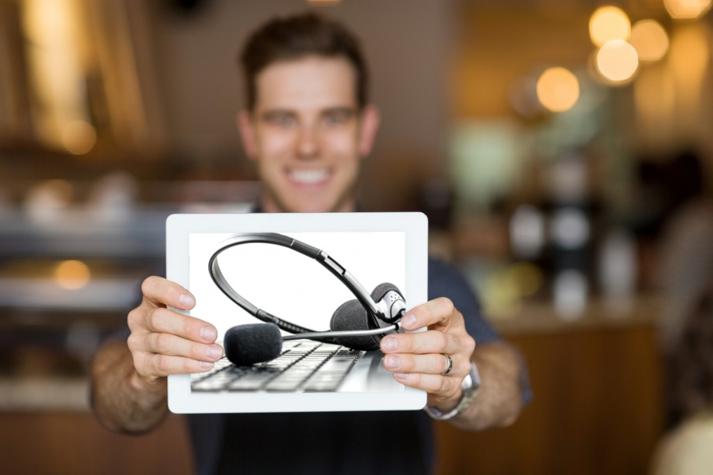 man holding a tablet showing a headset showing what he learned in a contact center